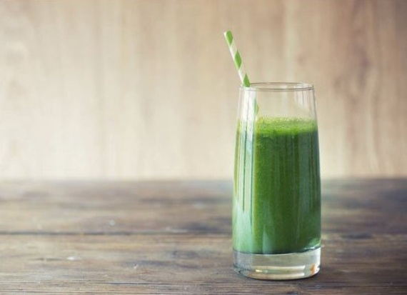Classic green monster energy pre-workout smoothie with green and white striped straw. Sitting on a wooden table.