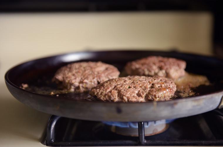Hamburger marinated patties on grilling