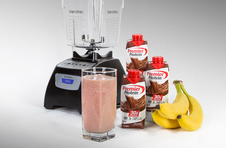 Chocolate Banana Protein Smoothie. Blendtec blender with 3 chocolate premier protein shakes and bananas zoomed in